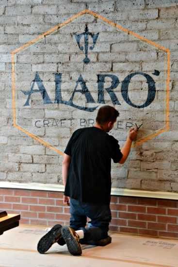 Alaro logo being painted onto an interior wall. Courtesy: Alaro Craft Brewery